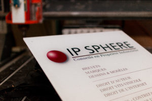 Plaque professionnelle gravée en plexiglas blanche posée sur un plan de travail avec un fond flou