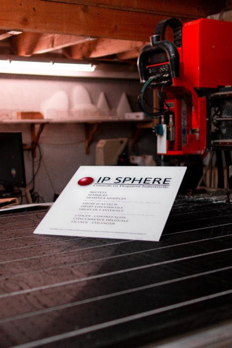 Gravure sur plaque professionnelle en plexiglas blanche posée sur un plan de travail
