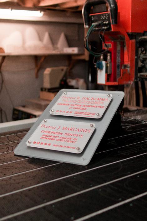 Plaque professionnelle en plexiglas gravée posée sur un plan de travail