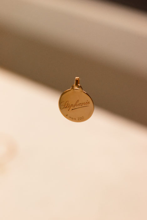 Gravure sur pendentif en plaqué or, suspendu avec un fond flou