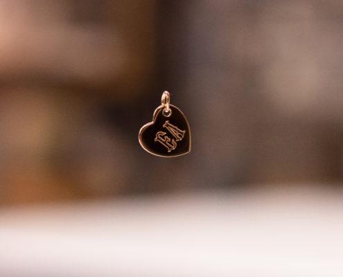 Pendentif en forme de coeur avec des initiales sur fond flou