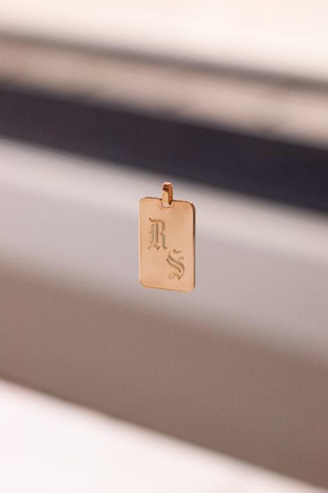 Pendentif en plaqué or avec des initiales, suspendu avec un fond flou
