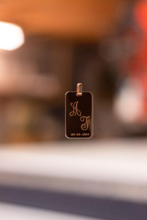 Pendentif gravé en plaqué or avec des initiales, suspendu avec un fond flou