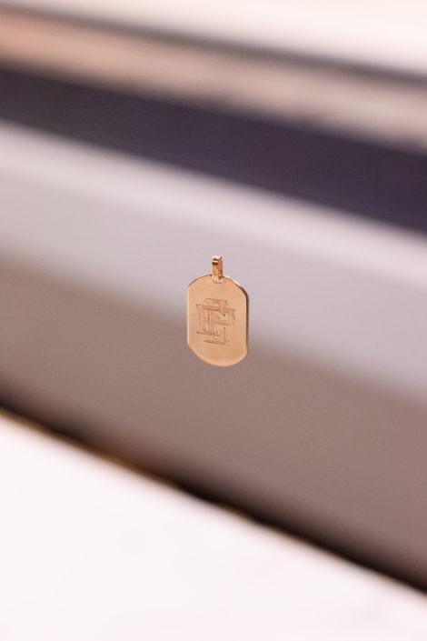 Pendentif gravé avec des initiales en monogramme / Plaqué or. Pendentif suspendu avec un fond flou
