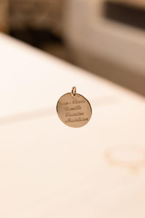 Pendentif rond en plaqué or gravé, suspendu avec un fond flou