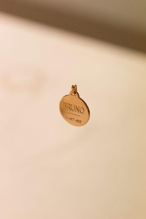 pendentif gravé en plaqué or, suspendu avec un fond flou