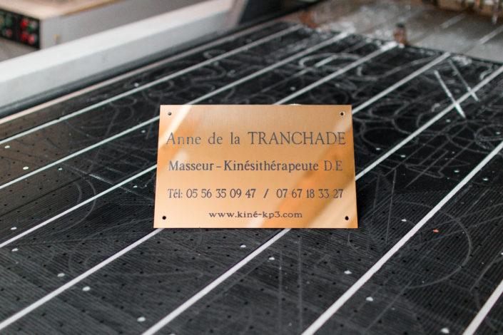 Plaque professionnelle en laiton gravée posée sur un plan de travail avec un fond flou
