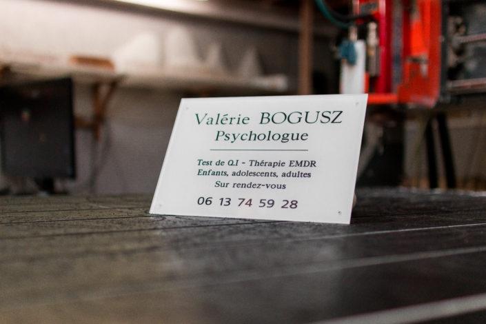 Plaque professionnelle en plexiglas blanche gravée posée sur un plan de travail avec un fond flou