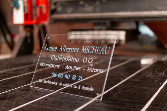 Plaque professionnelle gravée en plexiglas transparente posée sur un plan de travail avec un fond flou