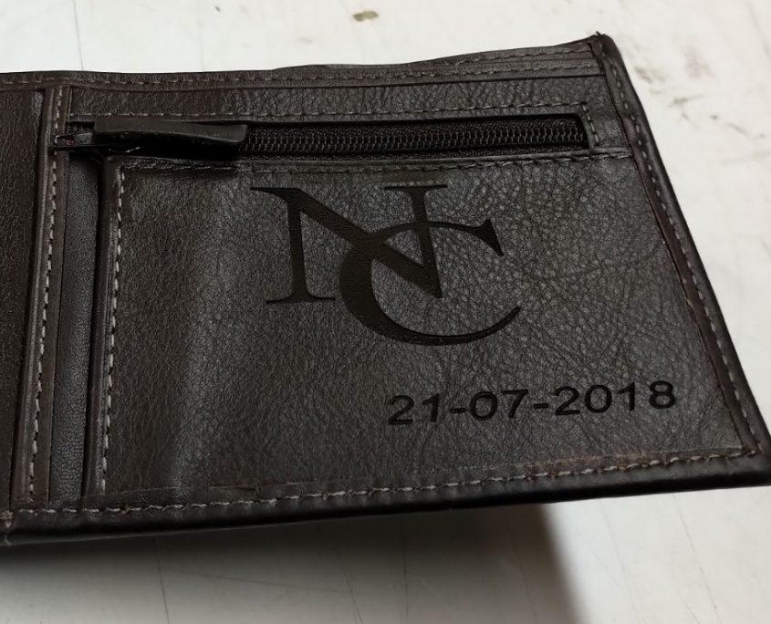 Gravure sur un porte-monnaie noir avec des initiales et une date