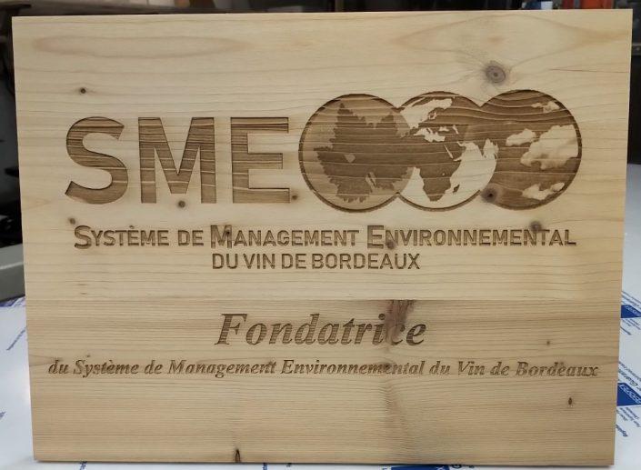 Gravure sur une planche en bois avec un logo et des inscriptions dessus