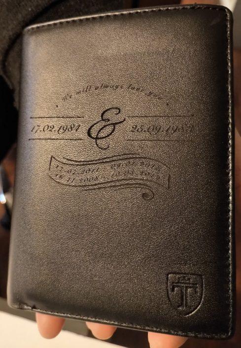 Gravure sur un porte-monnaie marron avec des inscriptions dessus et des dates