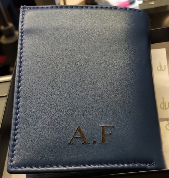 Gravure sur un porte-monnaie en cuir bleu avec des initiales