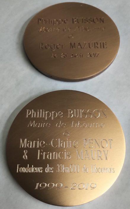 Gravure sur deux médailles avec des inscriptions et des dates dessus