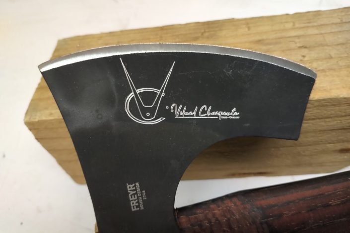 Gravure sur une hache en métal avec un logo et des inscriptions dessus