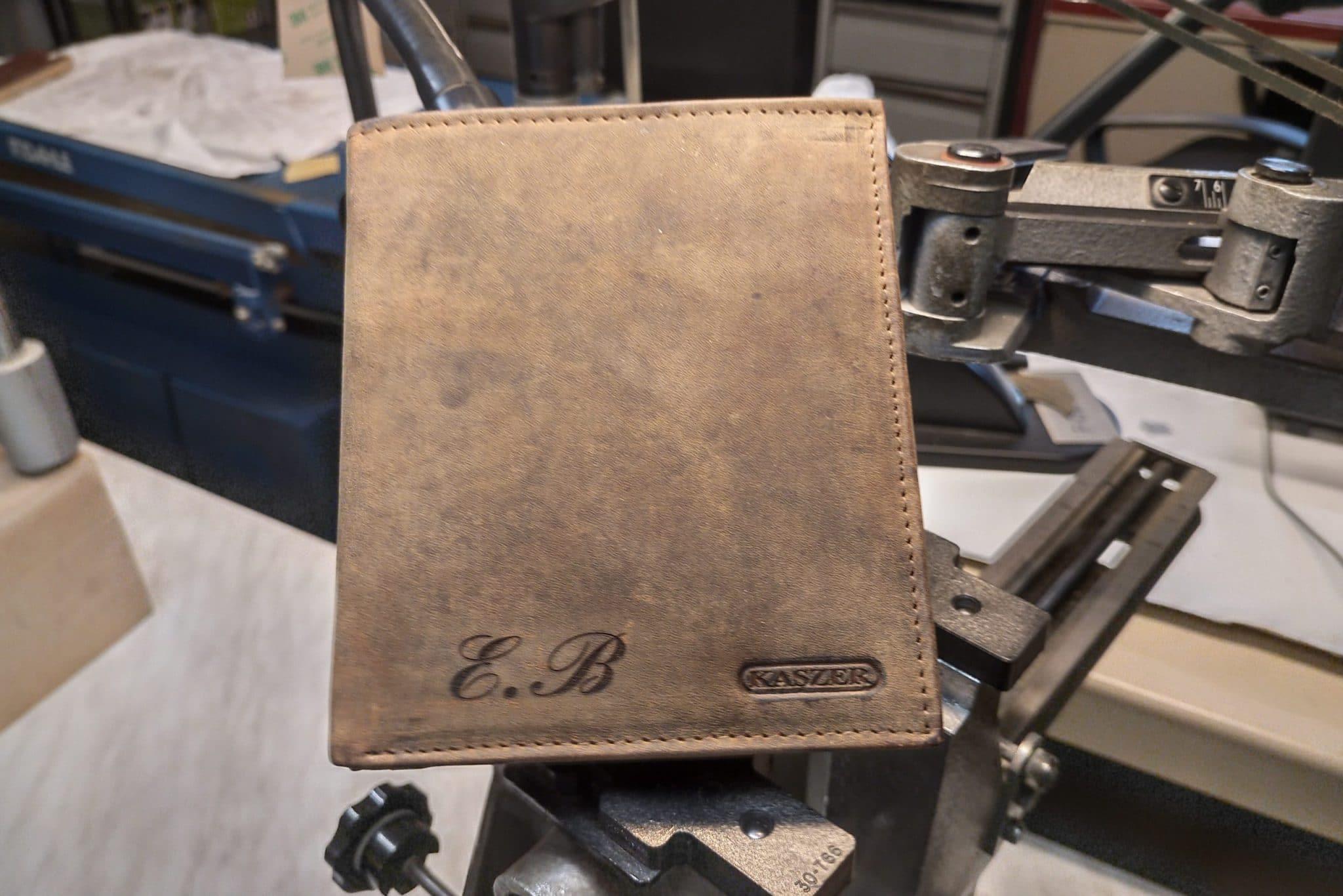 Gravure sur un porte-monnaie en cuir marron avec des initiales