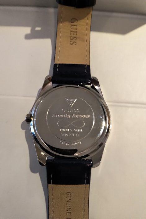 Gravure sur le derrière d'une montre avec symbole, prénom et date