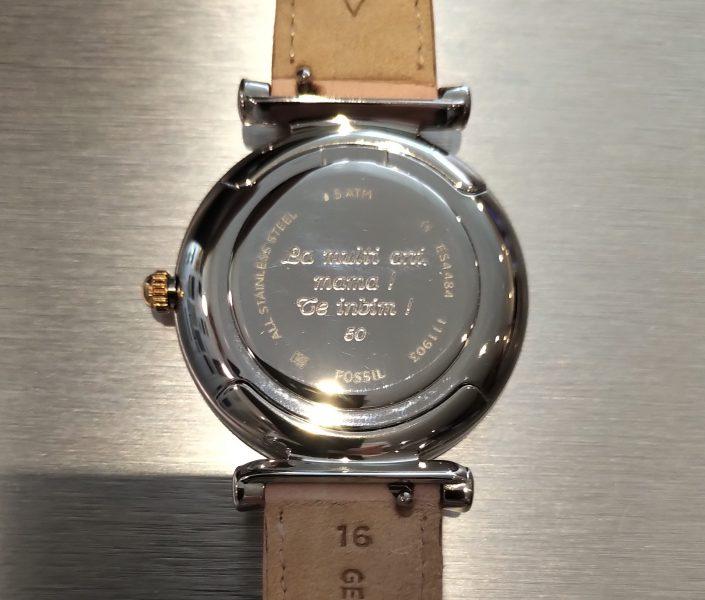 Gravure sur le dos d'une montre avec un texte